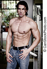 Handsome muscular man in jeans shirtless looking away,...