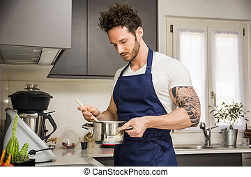 Handsome muscular man in kitchen, cooking