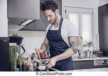 Handsome muscular man in kitchen, cooking