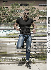 Handsome muscular man standing in city setting - Handsome...