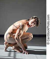 Handsome, muscular man totally naked, kneeling on the floor