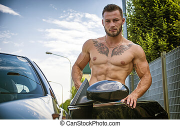 Handsome muscular man with tattooes getting in car