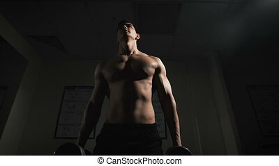 Handsome muscular man working out with dumbbells over dark background