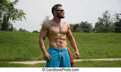 Handsome Muscular Shirtless Hunk Man Outdoor in City Park. Showing Healthy Muscle Body. Smiling at the end