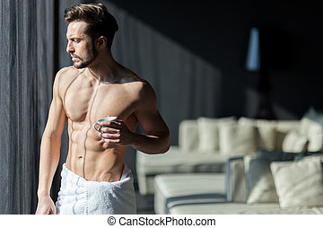 Handsome, muscular, young man drinking his morning coffee in a hotel room standing next to a window and looking against bright sunlight