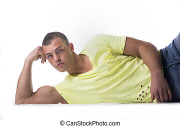 Handsome, muscular young man leaning on the floor