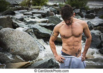 Handsome muscular young man outdoor wearing only towel