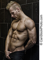 Handsome, muscular young man shirtless leaning against tiled wall