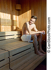 Handsome, muscular, young man sitting in a sauna alone thinking