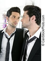 Handsome narcissistic young man looking in a mirror -...