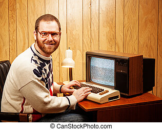A Handsome and Nerdy Adult using a Vintage Commodore Vic-20 64 computer on a Retro TV.