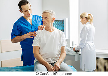 Handsome nice man touching his patients shoulder