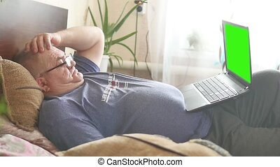 old man is using a laptop, looking at camera and smiling while lying in bed