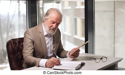 Handsome old man working on digital tablet in home office.