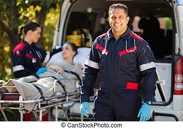 paramedic with colleague and patient on background -...