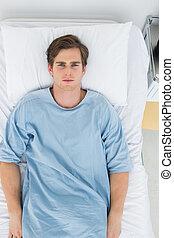 Handsome patient lying in bed - Overhead view of handsome ...