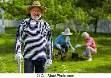 Handsome pensioner smiling while working in the garden