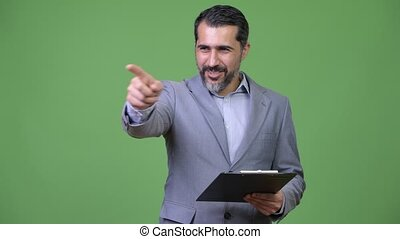 Handsome Persian bearded businessman directing while holding...
