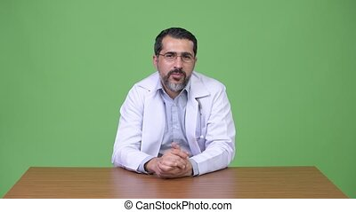 Handsome Persian bearded man doctor talking and giving...