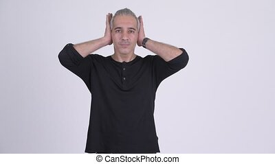 Handsome Persian man covering ears as three wise monkeys...