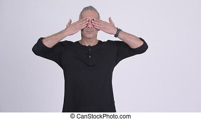 Handsome Persian man covering eyes as three wise monkeys...