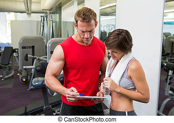 Handsome personal trainer with his client looking at...