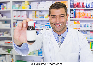 Handsome pharmacist showing medicine bottle at the hospital...