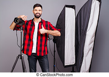 """Handsome photographer with camera in photo studio gesturing """"LIKE"""""""