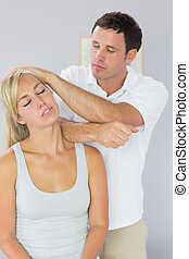 Handsome physiotherapist massaging patients neck with elbow