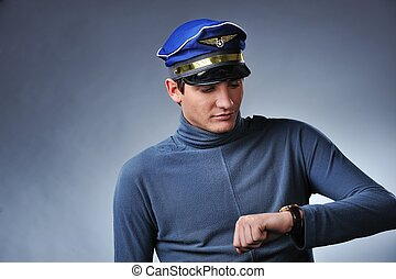 Handsome pilot looking to his watch. Isolated on grey background