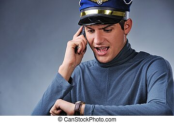 Handsome pilot talking on mobile phone