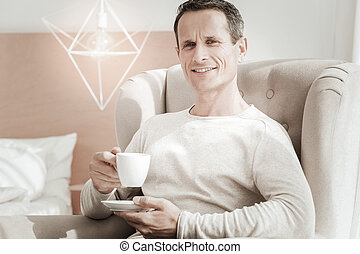 Handsome pleasant man holding a cup and smiling.