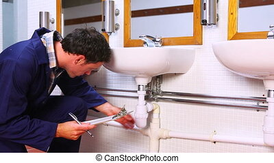 Handsome plumber looking at sink holding clipboard in a...