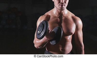 Handsome power athletic man with dumbbell confidently...