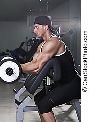 Handsome powerful athletic man doing biceps exercise with barbell. Strong bodybuilder with perfect muscles.