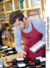 handsome professional sommelier choosing a bottle of wine