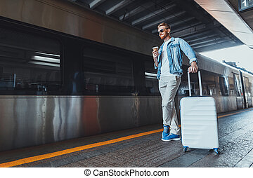 Handsome red haired man in sunglasses standing on platform at railway station