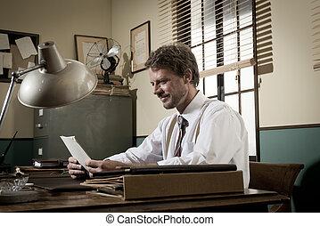 Handsome retro businessman reading a document