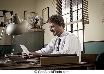 Handsome retro businessman reading a document