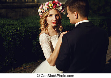 Handsome romantic groom looking at beautiful blonde bride with bouquet at sunset outdoors