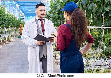 Handsome Scientist Talking to Female Worker