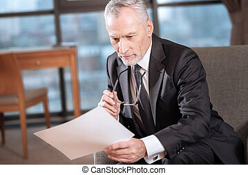 Handsome senior businessman  examining documents