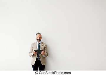 Handsome senior businessman with tablet by wall