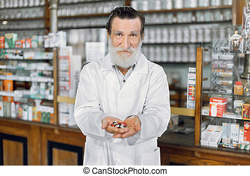 Handsome senior male pharmacist posing in ancient pharmacy interior and showing to camera handful of colorful different pills and capsules