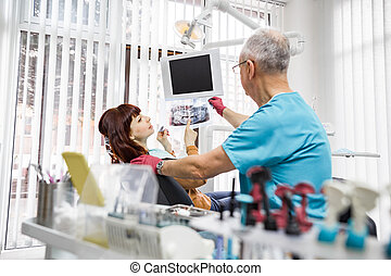 Handsome senior man dentist looking at x-ray image of his young smiling woman patient.