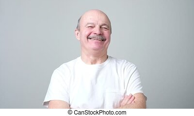 Handsome senior man in white t-shirt laughing. Positive...
