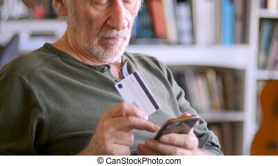 Handsome senior man ordering on his mobile phone online with...