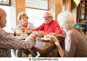 Handsome senior man sharing story with friends