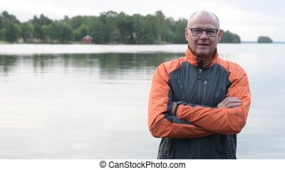 Handsome Senior Man Smiling By The Lake - Portrait of...