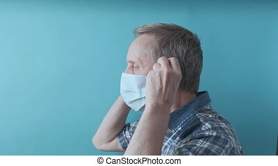 Handsome senior man takes off the medical mask on face and looking into camera on self-isolation at home. An elderly man takes off surgical mask. 4k footage